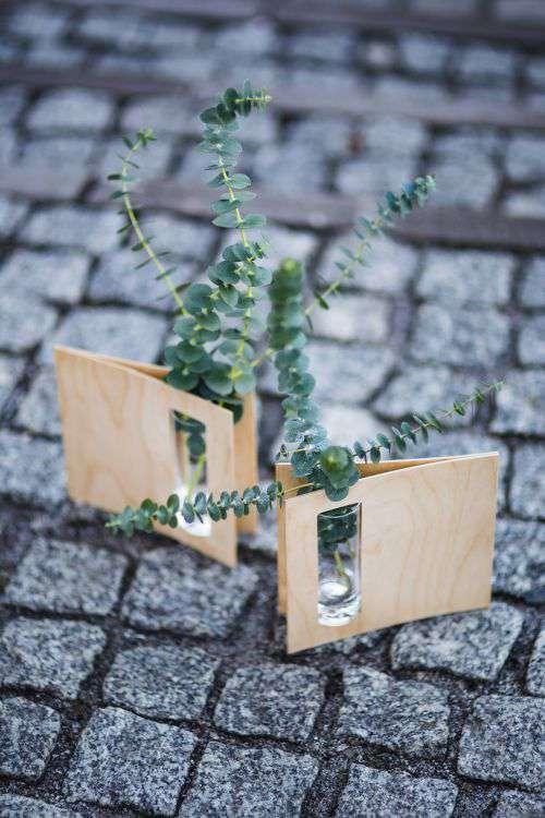 Miniature green plants in small glasses on cobblestone