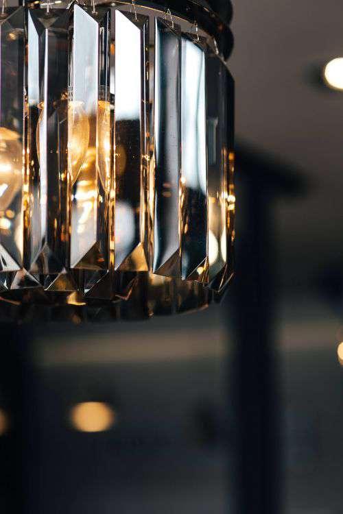 Elegant black designer chandelier with a lit lightbulb
