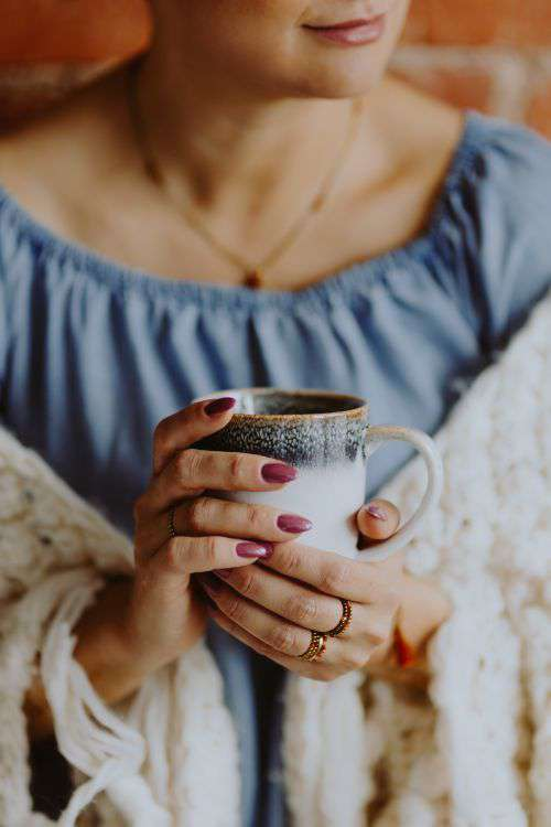 A woman in a warm blanket holds a cup of coffee or tea