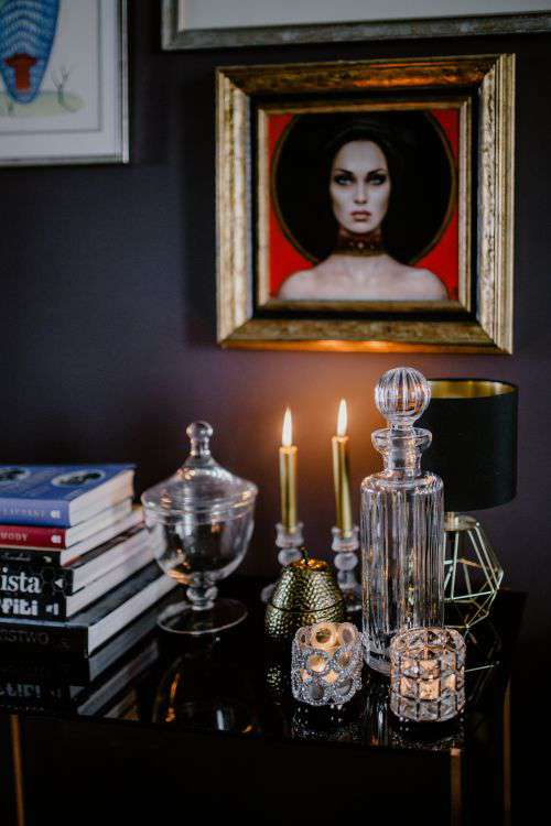 Decanter, candles, and a painting on the wall
