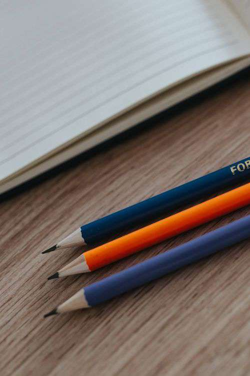 Notebooks with colourful pencils on a wooden desk