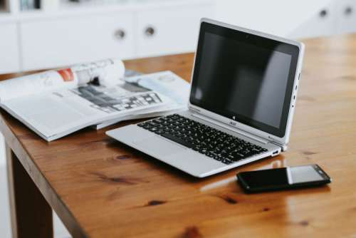 Silver laptop with various items on a table
