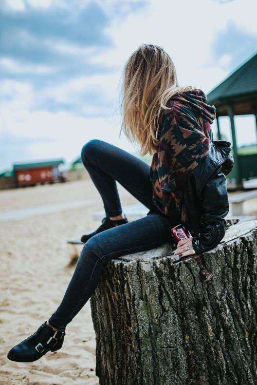 Beautiful blonde woman relaxing with a can of coke on a tree stump by the beach