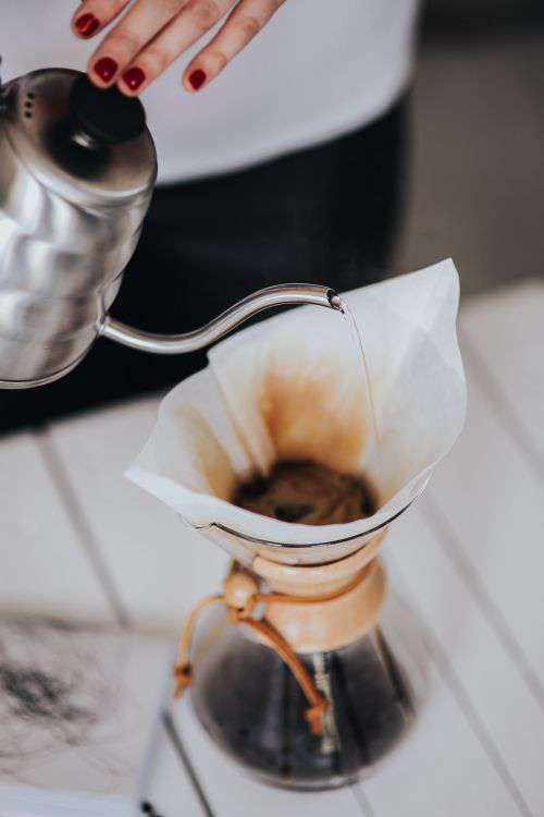 Woman pouring water in Chemex filter coffee maker