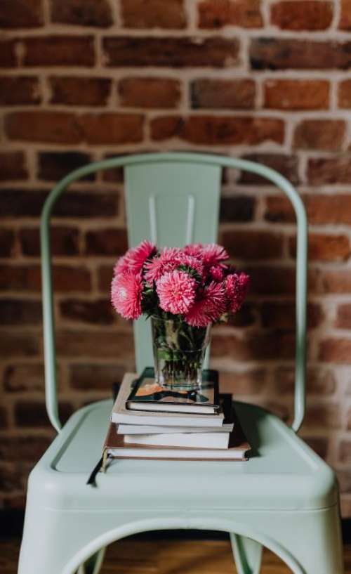 Industrial metal chair with a bouquet of pink flowers and books on it