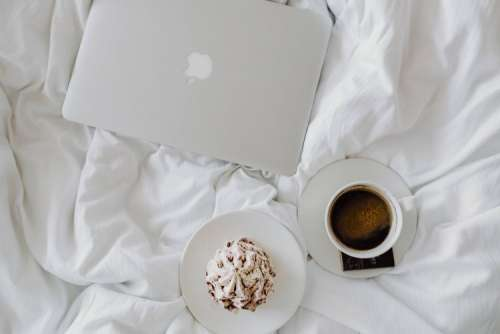 Woman working on a laptop while enjoying a breakfast coffee and chocolate in bed
