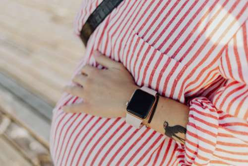 A pregnant woman with a smartwatch on her hand