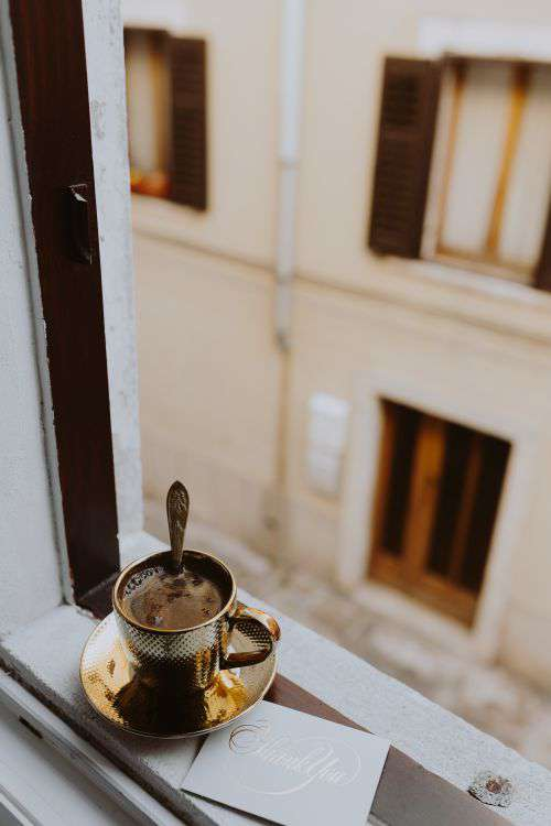Drink coffee in a golden cup at the window
