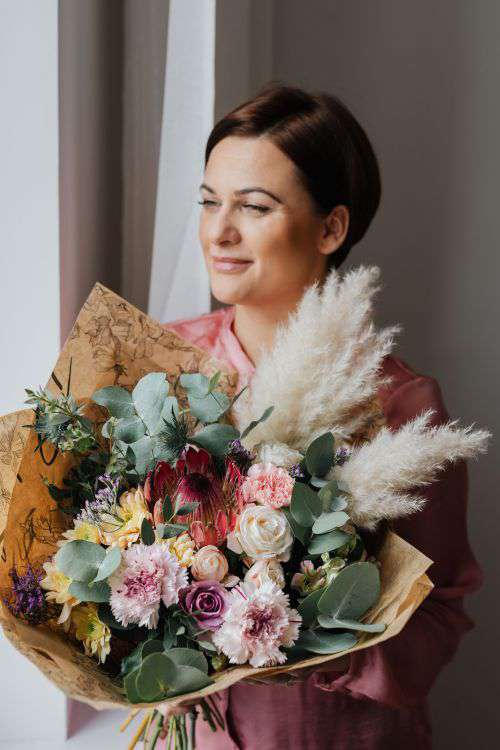 A woman with a bouquet wrapped in paper