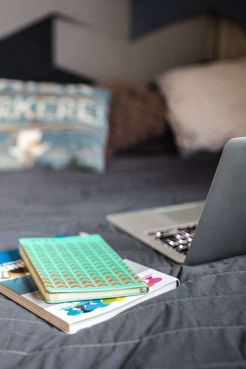 Laptop with books on a bed