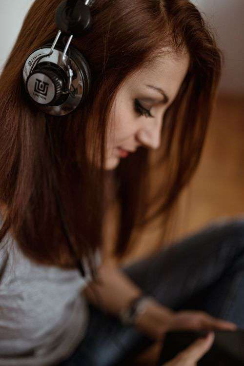 Beautiful young woman in headphones listening to music