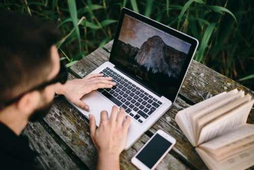Man working on Macbook at lake