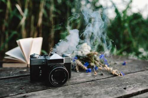 Colorful smoke bomb, book and vintage camera