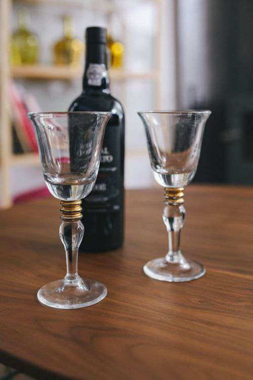 Two empty wine glasses with a bottle of wine on a table