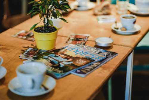 Laptop, a smartphone, magazines and cups of coffee on a table