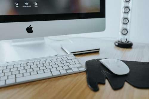 White Apple iMac computer with elephant mousepad