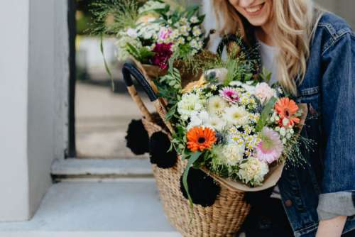 Young woman with basket full of flowers