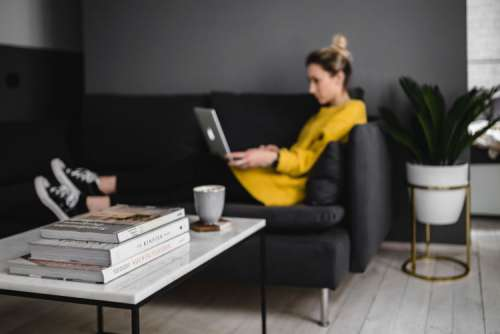Young woman sitting on the sofa and working on her laptop