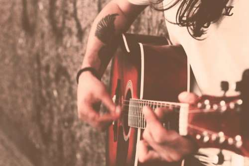 Musician Strumming Guitar Free Photo