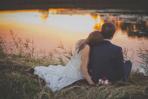 Wedding Couple on Grass at Sunset Free Photo