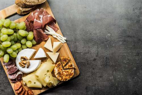 Tasting Cheese Dish on a Wooden Plate Free Photo