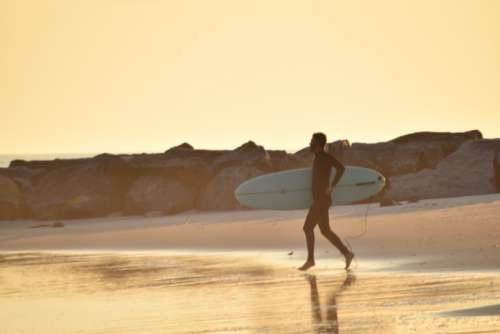 Surfer running with his surfboard to catch one more wave during golden hour.