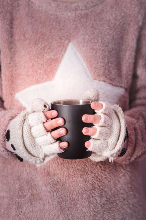 Female hands holding mug with hot drink