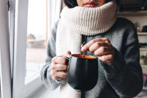 young woman stirs a hot drink with a spoon in a mug standing near a window