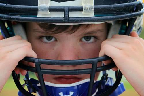 Portrait of young football player: Portrait, background, desktop, tabletop, people, human, face, expression, sports, sport, helmet, football, American football, athletics, athletic, athlete, drive, intense, one person, eyes, minimalistic, color, image, guard, equipment, youth, boy, no smile, team, league, season