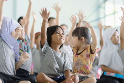Group of asian kids raise hand up at school.
