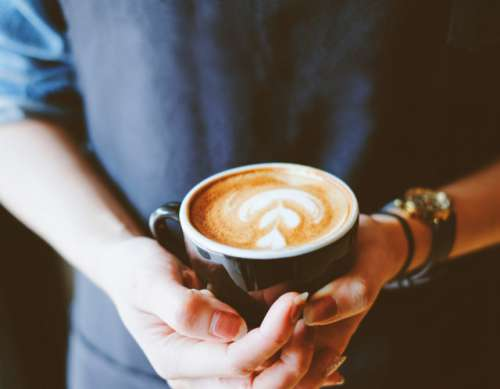 Barista holding hot cup of latte in the cafe