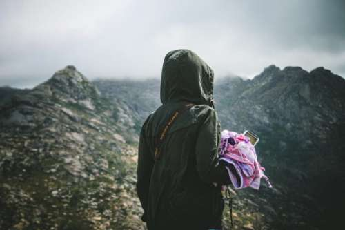 Millenial woman hiking in an inspirational moment. Adventure traveling.