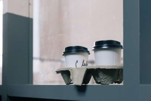 2 coffee in a paper cup on the windowsill