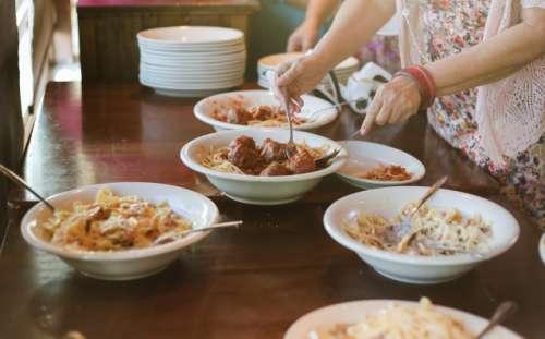 A woman serves herself pasta