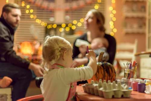 Little girl painting a pumpkin at a Halloween party while adults chat in the background  💫