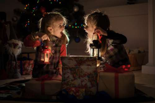 Christmas night. Two girls open the gifts under the tree. New year's stories. Real emotions.
