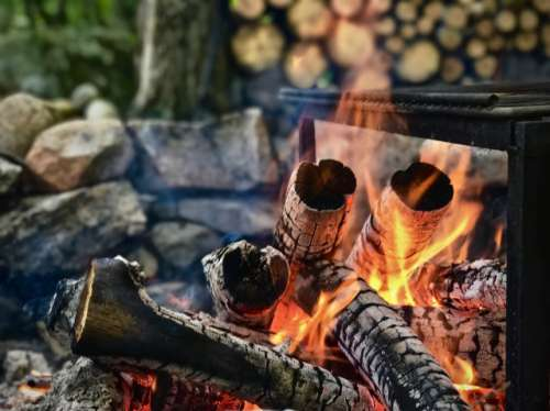 Closeup of bright orange campfire flames and burning wood