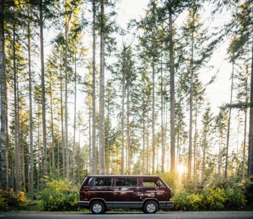 A maroon Volkswagen Vanagon sits in the sunset light