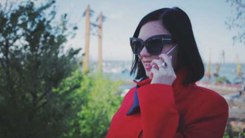 Portrait of young woman in red coat and cat eye sunglasses talking on her smartphone