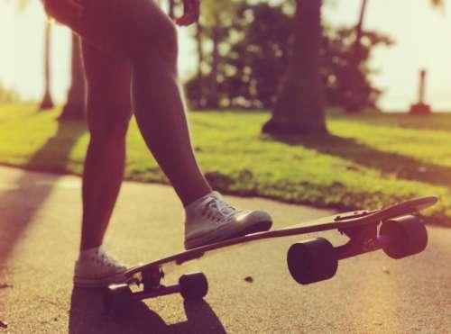 Woman cruising on a longboard in a park