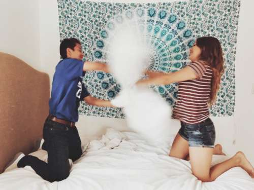 Cousins pillow fighting in the bedroom