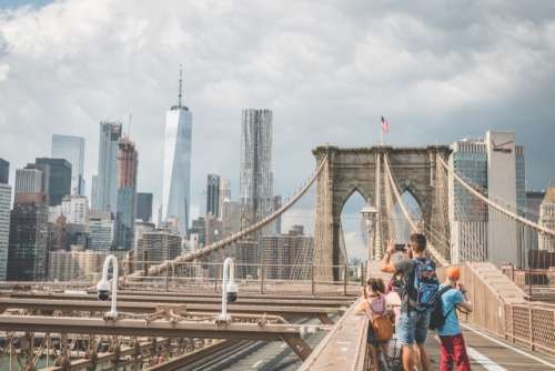 Man taking a photo on Brooklyn Bridge.