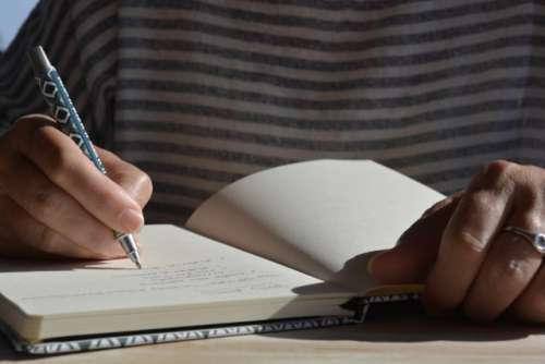 Woman writing in a journal, mid-section, low angle view