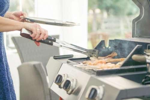 Woman grilling meat outside.