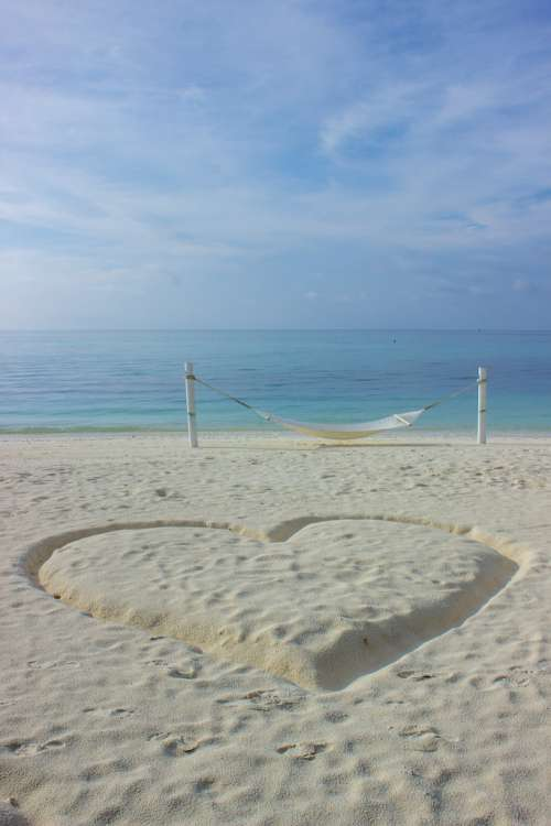 Heart Drawn in the Sand Next to a Hammock on a Beach