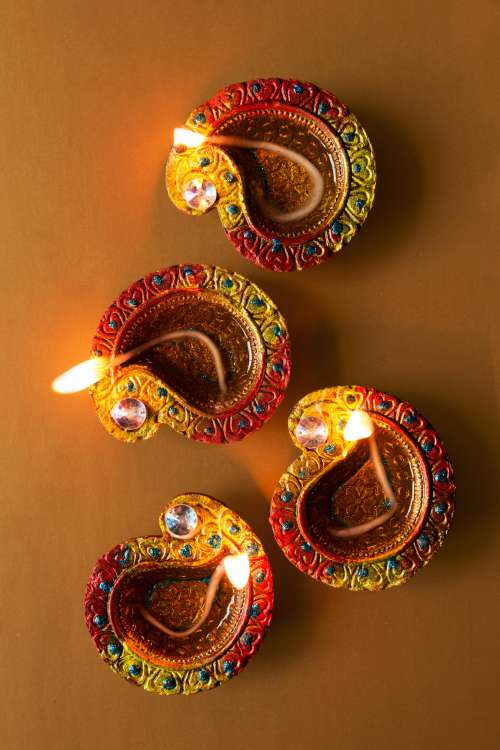 Four Candlelit Diya Lamps Rest On Brown Background Photo
