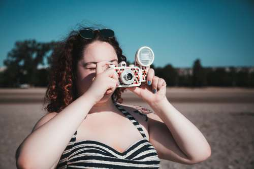 Young Woman In Sunglasses Taking Photograph On Beach Photo