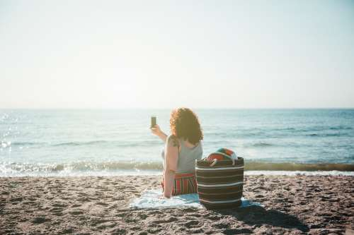 Young Woman Takes Selfie While Sitting On Sunny Beach Photo