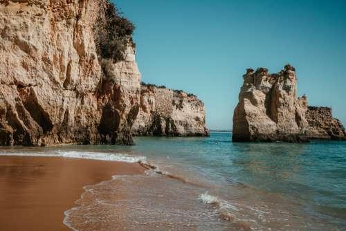 Sandy Beach By Rocky Cliffs Photo