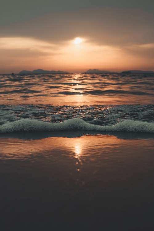 Sunset Casts Gradient Over Foaming Waves On The Shore Photo